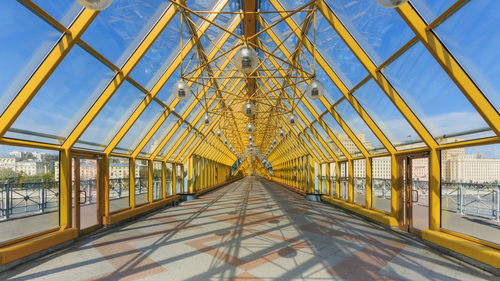 The Pushkinsky Bridge, with bright yellow frames between the panes of glass enclosing the deck