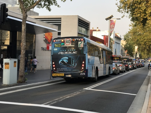 Photo of a bus with an advertisement reading 'ROGUE' driving in Chatswood