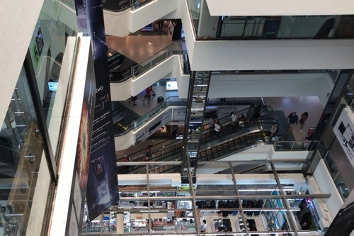 View inside Sim Lim Square, looking down from the top floor towards the concourse, with escalators.