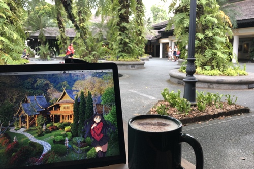 Stereotypical view of my laptop and a cup of coffee, with the visitor centre for the Singapore Botanic Gardens in the background, with plenty of trees and scenic stuff.