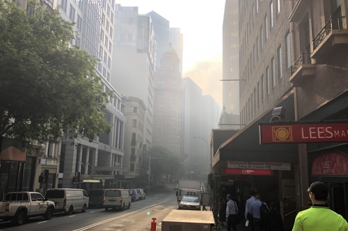 Photo looking down a street near Wynyard Station in Sydney, showing smoke shrouding the buildings on the next block.