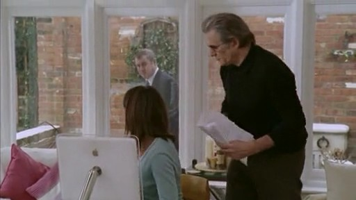 DCI Barnaby peering into a glass window at suspects, using an iMac G4.