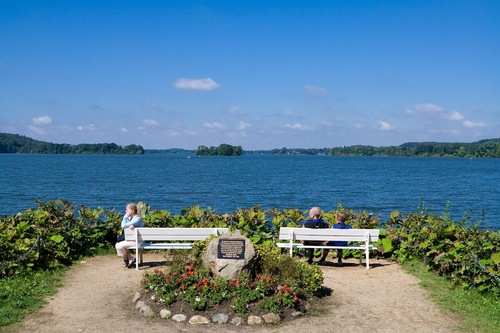 Photo of park benches overlooking a lake scene. A couple sits on the right bench, and a single woman on the left gazing into the distance.