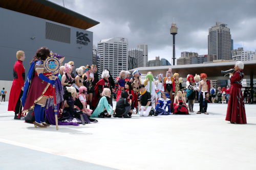 Photo outside on the International Convention Centre roof, with a crowd of Fate/Grand Order cosplayers and a staff member dressed as Emiya giving orders! Sydney is in the background