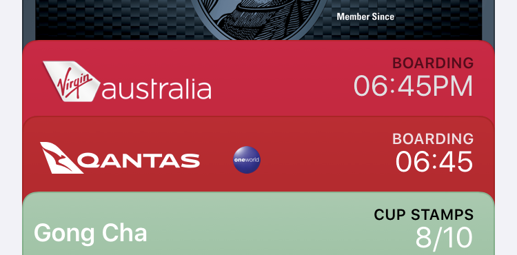 Apple Wallet showing two boarding passes. The first is a Virgin Australia with black boarding text on red, and the time 06:45PM in white. The second is Qantas with white boarding text on red, and the time 06:45