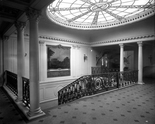 Photo of the landing of Aquitania's Grand Staircase. The stairs start to the left of the stairwell and wind clockwise down, compared to the symmetrical stairs of Olympic.