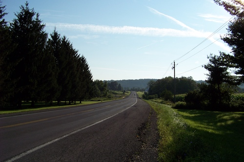 A two-lane highway heads through an area containing open fields and areas of trees. A large, tree-covered ridge is in the distant background.