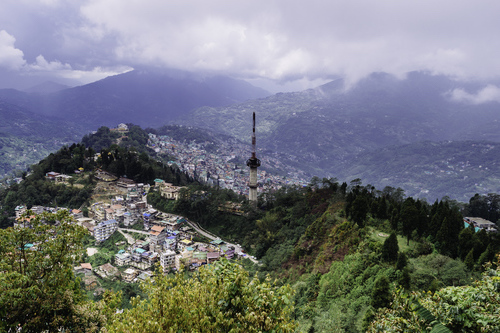 Photo of Gangtok showing the town, a communications tower, and a long valley capped with clouds.