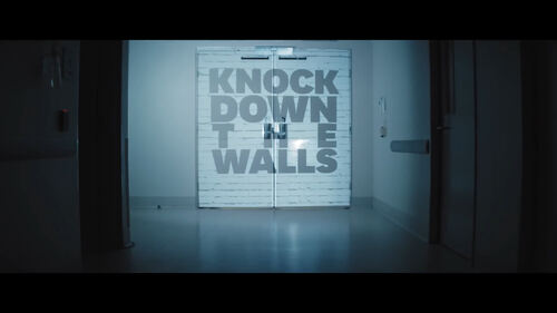 Photo of glass doors, with Knock Down the Walls written across them