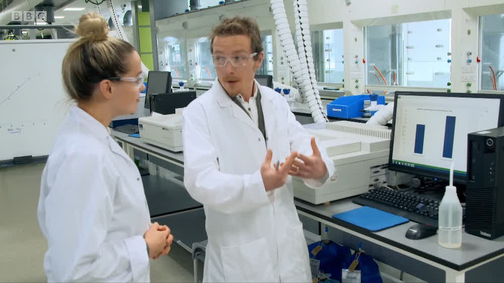 Screenshot showing the scientist and journalist in a lab with a mass spectrometer