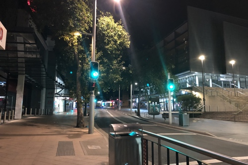 Photo late at night in Chatswood, showing an empty street and a green traffic light.