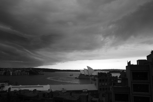 Black and white photo of the Opera House set under some scary rolling clouds.