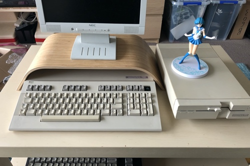 Photo showing the Commodore 128 snugly under an IKEA monitor stand with a 1571 disk drive.