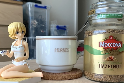 Photo showing Darjeeling holding a tea next to my cup of Moccona coffee.
