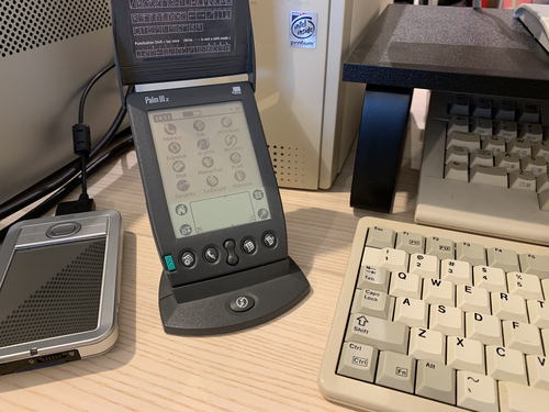 Photo of my Palm IIIx, with a Palm LifeDrive to the right, my Pentium tower from my childhood behind it, and a Commodore 128 off to the side.