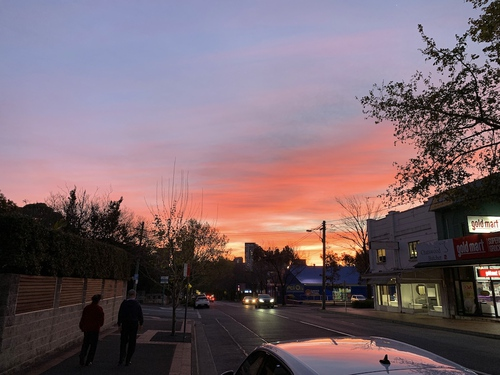 A deep pink, yellow, and red sunset over a suburban street in Chatswood, in the north of Sydney, in Australia, on Earth.