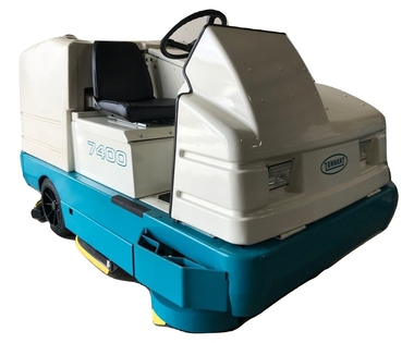Photo of a small, ride-on floor sweeping machine.