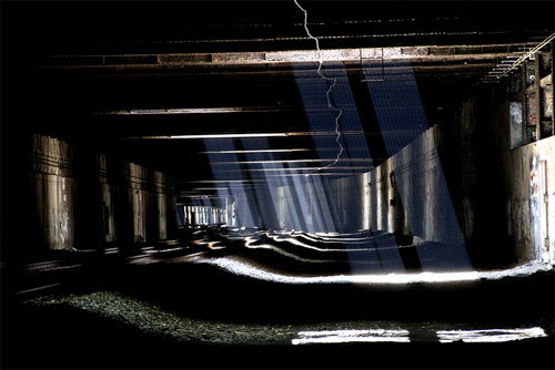 Photo of a dingy tunnel or underground room with light permiating through broken beams, quite beautiful
