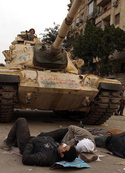 Photo of protestors sleeping in front of an army tank
