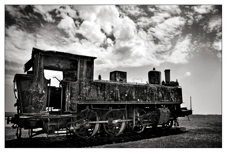 Monochromatic photo of an abandoned, rusting tank engine