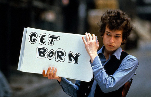 Bob Dylan holding up his famous Get Born sign