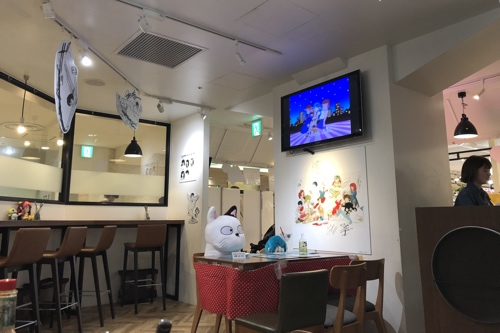 View inside popup cafe with TV showing an episode of Urusei Yatsura, and plushies!