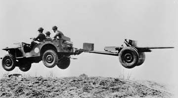 Bantam car in mid-air, taken 1940. Photo from Wikimedia Commons, released to the public domain as a work of the United States government