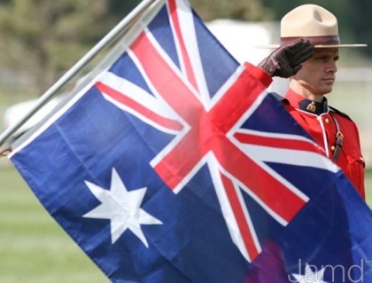 A Royal Canadian Mounted Police officer salutes behind the flag of Australia