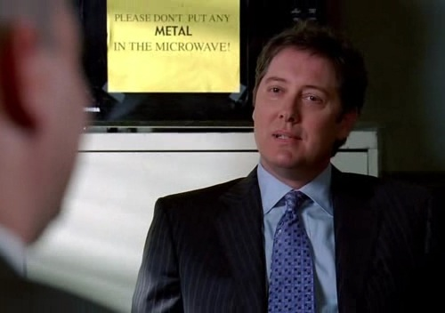 Screenshot from Boston Legal with a sign in the background that reads: Do not place metal in the microwave
